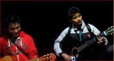 Unos adolescentes cantan con guitarra en mano.
